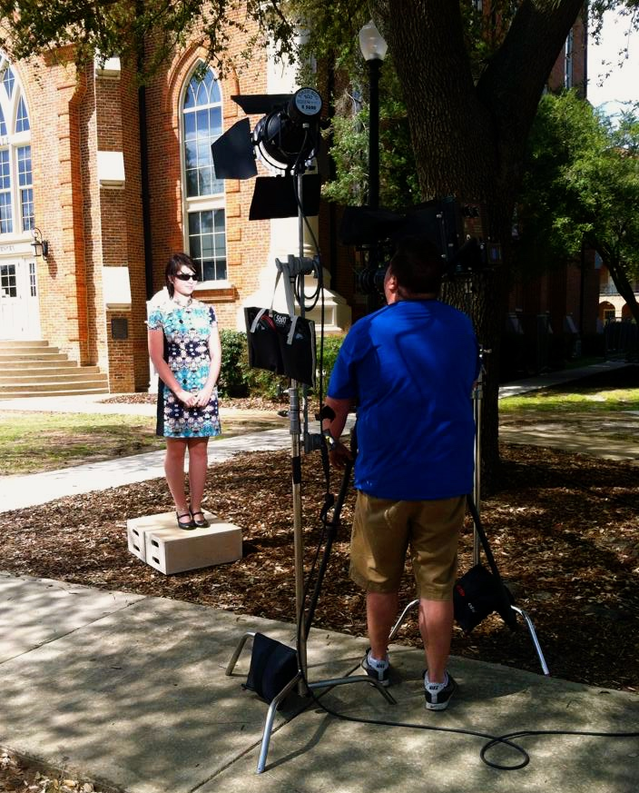 camera filming a student in front of Clark Hall