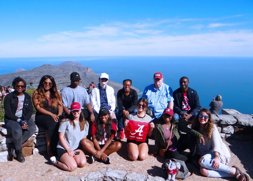 a group of students poses atop a mountain