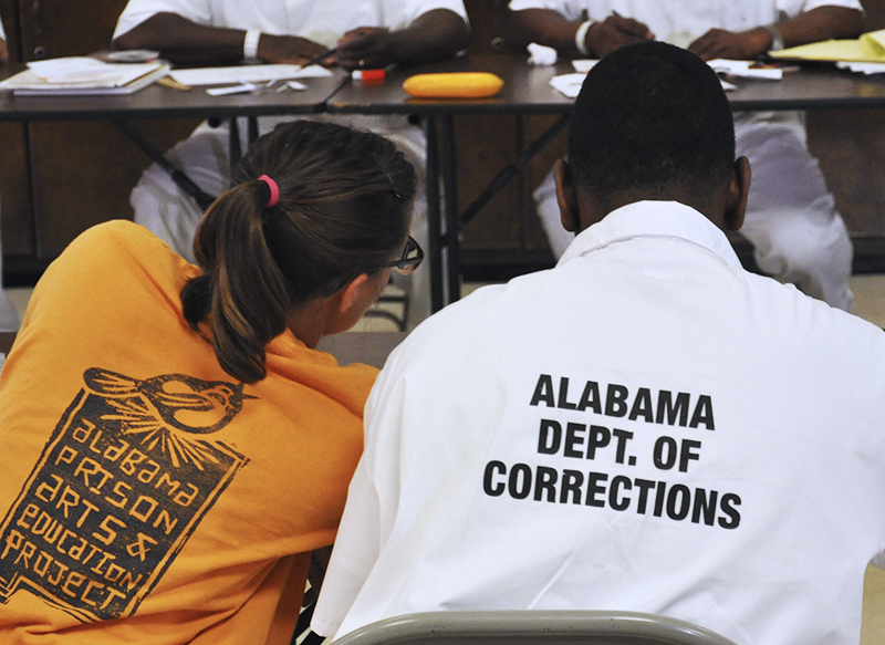 a teacher sitting next to a prisoner